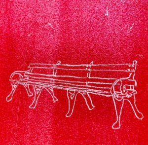a red square with a white line drawing of a park bench
