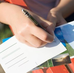 a hand with a pen, writing on postcards, on a sunny day
